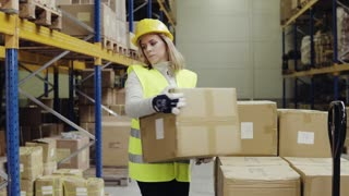 Young woman warehouse worker unloading boxes from a pallet truck