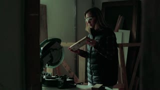 Young woman worker in workroom. Female carpenter using miter saw