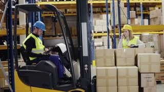 Young workers with smartphone in a warehouse. Man sitting in a forklift. Woman talking on the phone