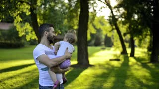 Young hipster father holding his little daughter in his arms, kissing her, sunny summer day outside in park