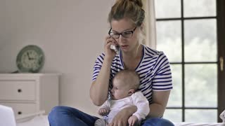 Young mother with baby son, sitting on bed, holding a smart phone, making a phone call, working on notebook, home office,