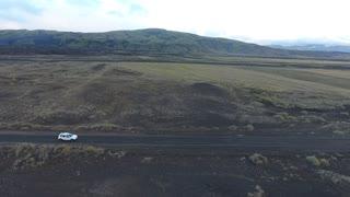 Aerial drone shot of a car driving offroad in Iceland. Sideway, medium altitude flight