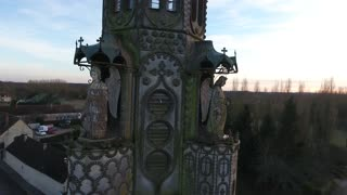 Aerial drone view flying around a chapel in a small village in France. Stone angels decoration. Sunset time