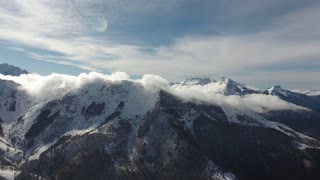 Aerial time lapse of clouds disappearing on snowy mountains. Sunny day in France