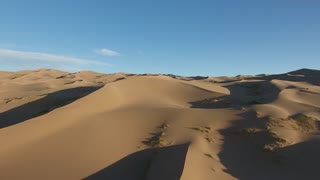 beautiful aerial drone shot over sand dunes in gobi desert golden hour