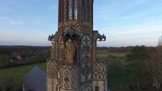 Close aerial drone view flying around a chapel in a small village in France. Stone angels decoration. Sunset time