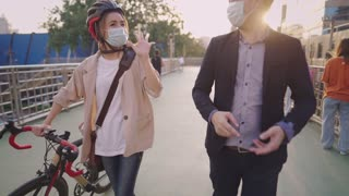 Young adult couple talking home together, sharing stories in a day while pushing bicycle through modern city overpass across busy road below, happy moment  strolling outside in new normal