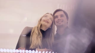 A beautiful young couple in a shop. A girl and a guy choose gifts for themselves. Camera movement through the display case, slow motion