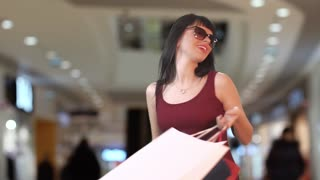 A good day for shopping. Girl with shopping bags in a shopping center. Slow motion