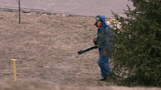 A man in a chemical protection suit and gas mask handles the territory from ticks.