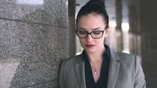 Attractive young woman with beautiful blue eyes wearing glasses thinking about something very important for her work