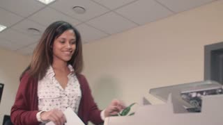 Beautiful African American girl, prints documents on the printer