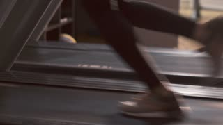 Beautiful girl in a gym running on a treadmill. 4K (UHD).