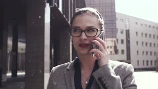 Business woman with glasses talking on the phone in the rain. Drops slowly fall. Slow motion.