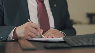 Businessman signing documents in his office. close-up