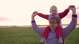 Father carrying daughter on his shoulders and plays with her. During sunset in a field