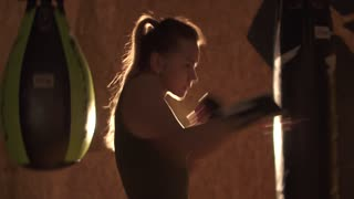 Girl kickboxer is preparing for the fight. Achieving goal. Preparation for competitions. 4K (UHD)