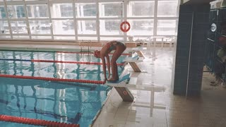 Jump into the water in the pool. The swimmer dives and swims under the water. The camera flies over it. View from above.