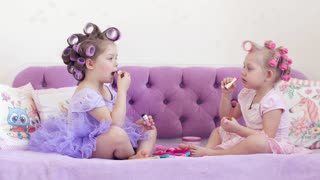 Little girls in hair curlers paint lips on a bed. 4k