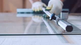 man cutting glass with glass cutter