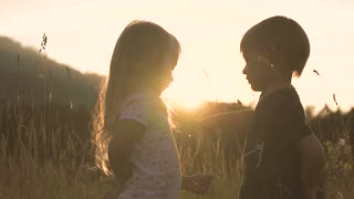 silhouette Boy giving a flower to girl on a background of clouds at sunset