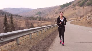 Sports girl runs up the hill. Beautiful scenery. Slow motion.