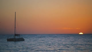 Sunset sea landscape on summer day, peaceful beach waves with boat sailing in the horizon