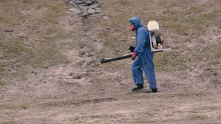 the destruction of ticks. Man in chemical protection suit.