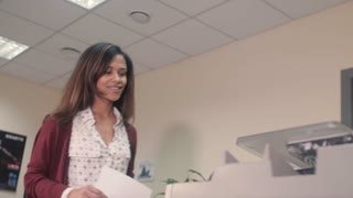 The young girl printing in the office