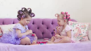 Two little girls in curlers make up. 4k