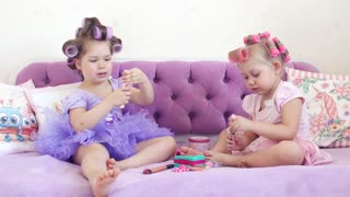 Two little girls in curlers use makeup. 4K