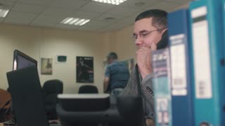 Young and ambitious stock market trader is doing a deal over the phone in a busy office filled with computers. The rest of his team are hard at work in the background