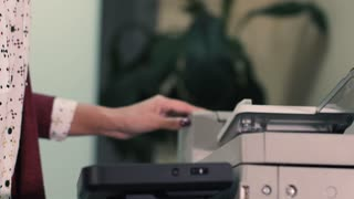 Young girl typing at office documents, pressing a button, turns on the printer