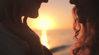 young loving couple on the seashore at dawn