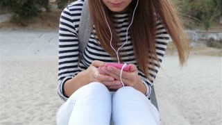Attractive young woman in a striped T-shirt listening to music with headphones on the beach