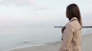Beautiful elegant young woman in a beige coat standing on the beach and looks at sea in the evening