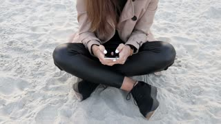 Beautiful elegant young woman in beige coat and black pants sitting on the beach and uses mobile phone