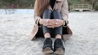 Beautiful elegant young woman in beige coat and black pants sitting on the beach