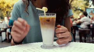 Close-up of a woman in a cafe drinking coffee with milk and ice