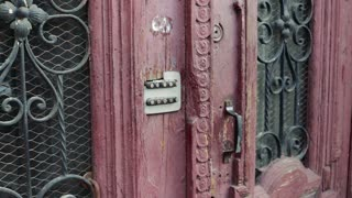 Female hand entering the secret code on the old door with a combination lock