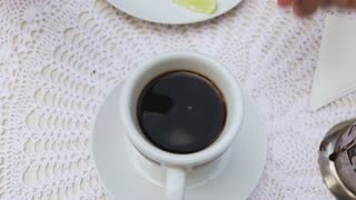 Female hand stirring coffee in the cup