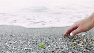Female hand touches sea water on the beach