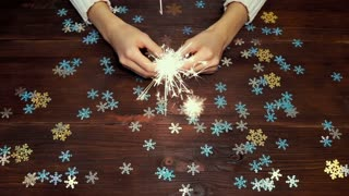 Female hands holding a burning sparkler over wooden table with decorations