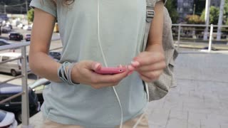 Girl connects the headphones to a mobile phone and listening to music in the city in the summer