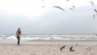 Girl feeding seagulls on the beach on a cloudy day, slow motion, wide shot