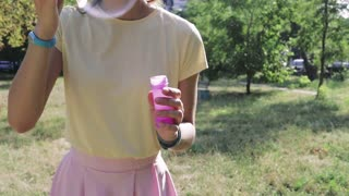 Girl in a yellow T-shirt and pink skirt blowing bubbles in the park in the summer