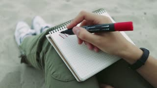Girl on the beach in the evening writing in a notebook with red felt-tip pen inscription