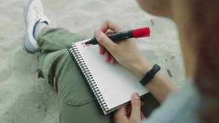 Girl on the beach writing in a notebook with red felt-tip pen task