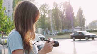 Slender brunette with a camera in the city in the summer