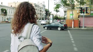 Slender woman with curly hair and a backpack waiting for the green traffic light at pedestrian crossing